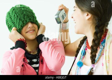 Zwei junge Freundinnen, eine Aufnahme Foto des anderen während sie Hut über die Augen zieht - Stockfoto
