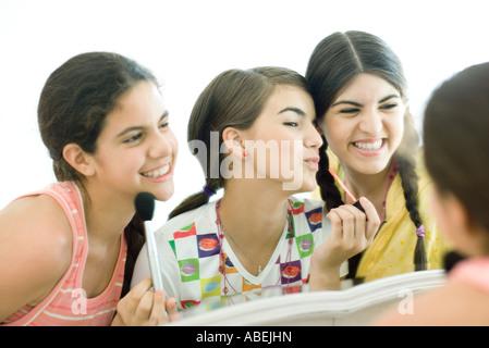 Drei jungen Freundinnen setzen auf make-up - Stockfoto