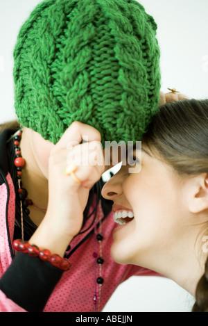 Zwei junge Freundinnen mit Köpfen zusammen, man zieht stricken Hut über Augen, während die andere lacht - Stockfoto