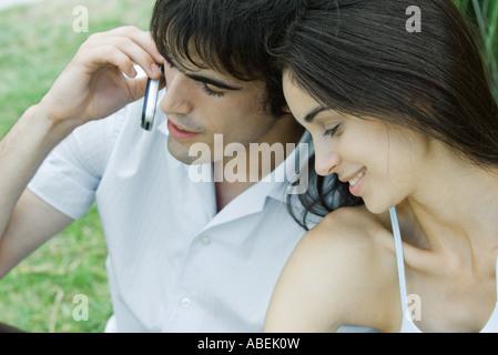 Junges Paar sitzt nahe beieinander liegen, Mann mit Handy - Stockfoto