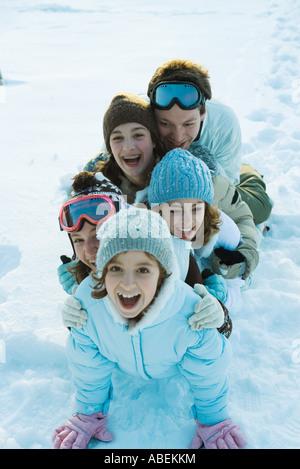 Junge Freunde, gekleidet in Ski-Kleidung, sitzen im Schnee, Porträt - Stockfoto