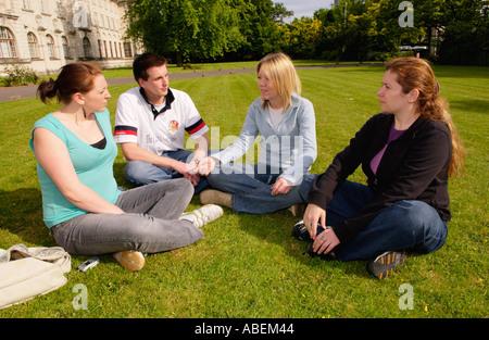 Cardiff University Studenten entspannen & im Chat auf dem Rasen im Sommersonnenschein an der Universität Cardiff - Stockfoto