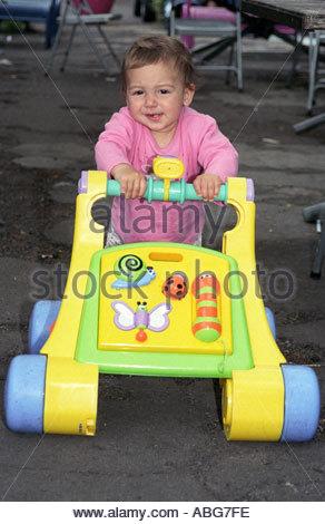 Babymädchen lernen, zu Fuß, mit einem Baby Kinderwagen Spielzeug UK - Stockfoto