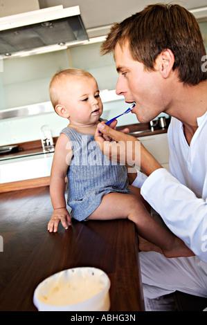 Vater und Baby in Küche, Mann Fütterung sein Sohn im Haus - Stockfoto