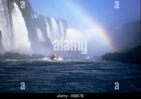 Iguaçu-Wasserfälle, Brasilien. Touristischen Schlauchboot nähert sich die Fälle mit Regenbogen. - Stockfoto