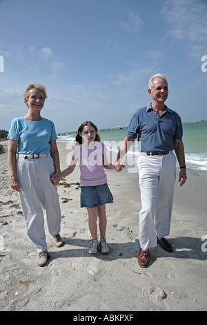 Foto von pensionierten älteres Paar mit ihrer Enkelin Händchenhalten und weißen Sandstrand am Meer schlendern - Stockfoto