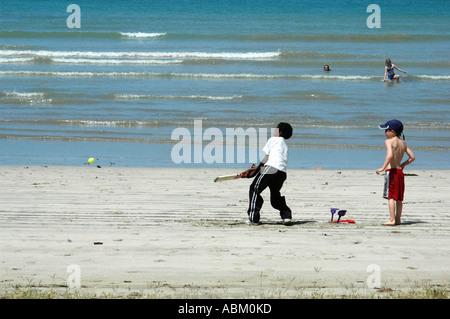 Jungen spielen Cricket am Strand - Stockfoto