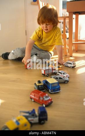 Kleiner Junge spielt auf dem Boden mit Spielzeugautos - Stockfoto