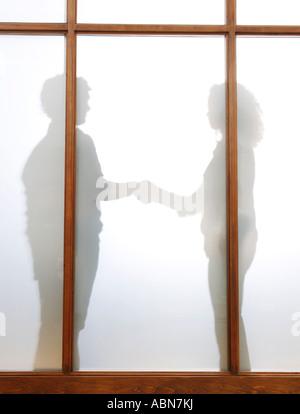 Silhouette von Geschäftsleuten, die Hände schütteln - Stockfoto