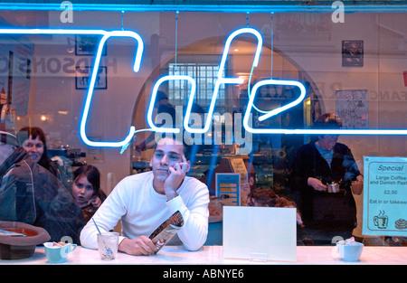 Junge Städter Blick aus Fenster Kaffeebar mit Leuchtreklame - Stockfoto