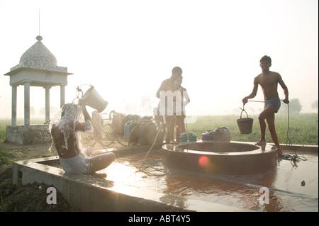 Männer, die ihre tägliche Dämmerung rituelle Waschung mit Wasser aus einem Brunnen mit Blick auf ihren Feldern in - Stockfoto