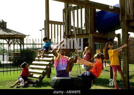 kleinen Kindern gemischt ethnische spielen und Klettern auf Anlagen im park - Stockfoto