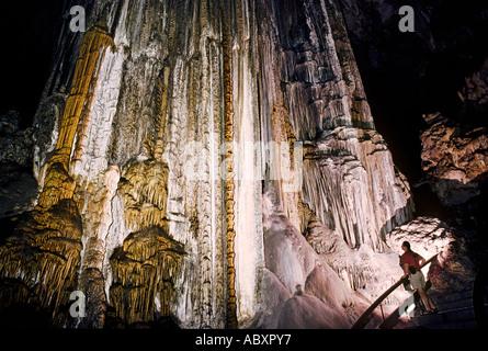 Weibliche Touristen vor riesigen Schmelzstein Spalte Bildung in Cueva de Nerja Malaga Spanien - Stockfoto