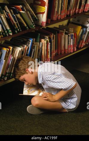 Kurzsichtiges Kind versucht, Grundschule lesen Bücher England London. 1980er Jahre. HOMER SYKES - Stockfoto