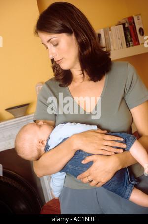 Mutter rockt ihr Baby Sohn schlafen - Stockfoto