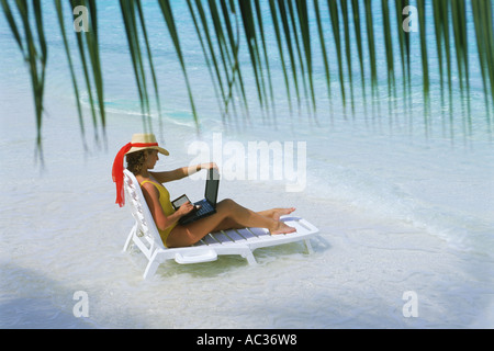 Frau sitzt am Sandstrand im Strandkorb mit Laptop während Arbeitsurlaub - Stockfoto