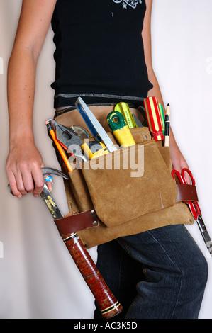 Junge skinny Bauarbeiter mit Werkzeuggürtel - Stockfoto