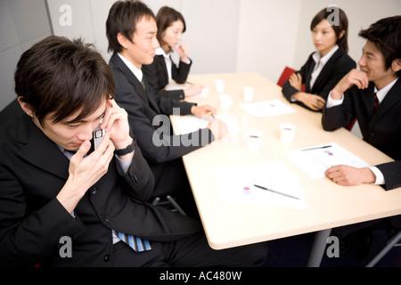 Junger Geschäftsmann mit Handy während der Sitzung - Stockfoto