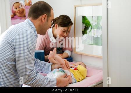 Junge Eltern am Wickeltisch, Vater wechselnden Windeln - Stockfoto