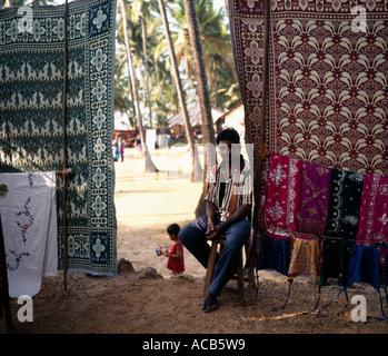 Kleidung-Stall und Standbesitzer in Anjuna Hippiemarkt, Goa, Indien, - Stockfoto