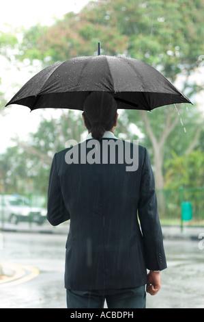 Rückansicht eines Mitte erwachsenen Mannes hält einen Regenschirm - Stockfoto