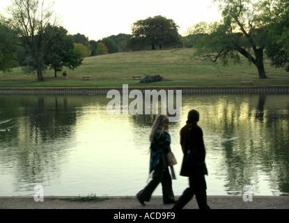 Paare, die im Park neben Teich auf Hampstead Heath - Stockfoto