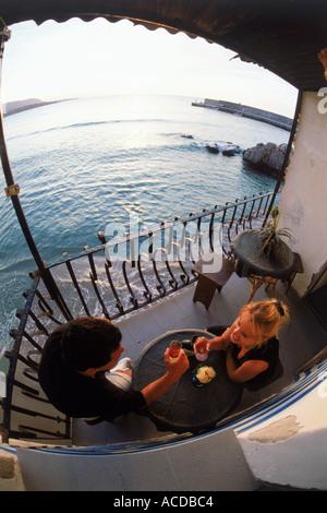 Zu zweit am Tisch mit Getränken auf Restaurant-Balkon über Mittelmeer bei Sonnenuntergang im Dorf von Cefalu auf - Stockfoto