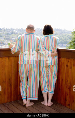 Paar auf Terrasse in passenden Pyjamas - Stockfoto