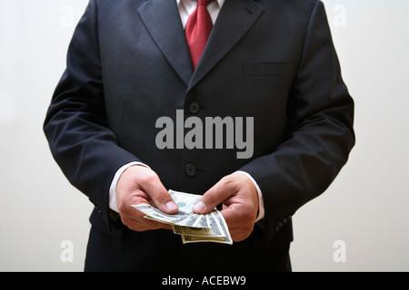 Geschäftsmann hält Stapel von 100-Dollar-Scheine - Stockfoto