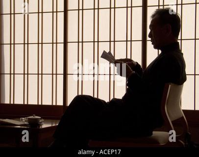 Silhouette der Mann vor Shoji-Bildschirm entspannt Zeitung lesen und einer Tasse Tee aus Japan - Stockfoto