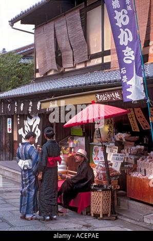 Touristen tragen Sommer Yukata stoppen, Chat mit Mann ruht auf Bank im historischen Bezirk von Kyoto - Stockfoto