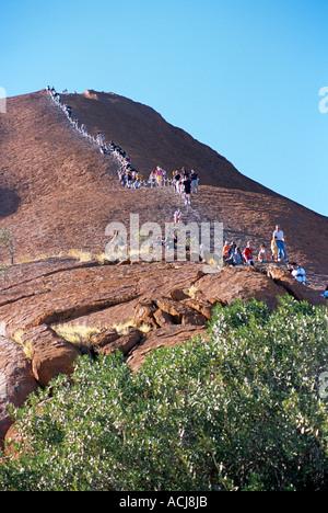 Montieren Sie Uluru, Uluru, Kata Tjuta Nationalpark, Northern Territory, Australien. Menschen klettern - Stockfoto