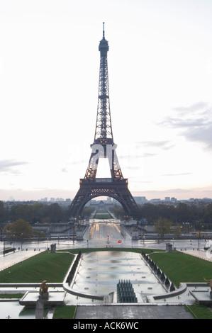 Der Eiffelturm in Paris im frühen Morgengrauen mit der aufgehenden Sonne am Horizont, hellblau sky, einige weiße - Stockfoto