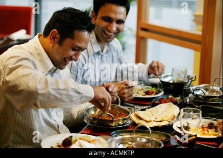 Zwei asiatische Männer genießen ein Balti-Essen in einem Restaurant in der Ladypool Road in Birmingham, UK - Stockfoto