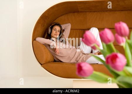 Junge Frau lag auf Sofa, tragen von Kopfhörern - Stockfoto