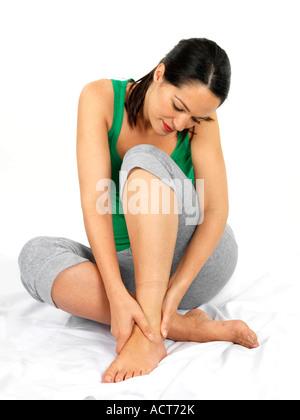 Junge Frau mit Knöchelverletzung halten ihren Knöchel Schmerzen und Beschwerden gegen einen weißen Hintergrund mit - Stockfoto