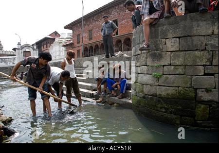 Männer auf der Suche nach Münzen und Schmuck in der Nähe der Feuerbestattung Ghats am Bagmati Fluss. Pashupatinath - Stockfoto