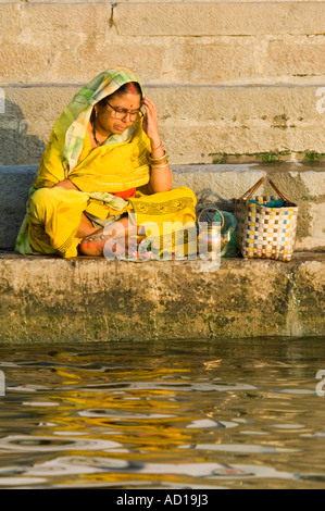 Eine indische Frau sitzt Schneidersitz im Gebet an die Kedar Ghat in Varanasi. - Stockfoto