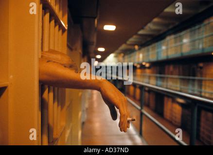Mannes Arme hand außen Gefängniszelle, rauchte eine Zigarette. - Stockfoto