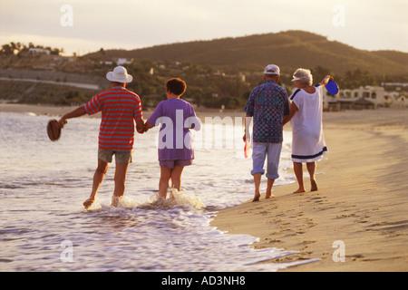 Ältere Paare, die zu Fuß durch Welle am Strand von San Jose del Cabo in Baja, Mexiko - Stockfoto