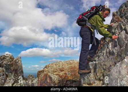 Eine Dame Kletterer absteigend einen steilen Abschnitt auf dem sehr schmalen und exponierten Crib Goch Grat in Nord - Stockfoto