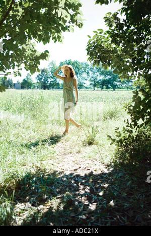Junge Frau trägt Sommerkleid und Sonnenhut, ein Spaziergang durch Feld - Stockfoto