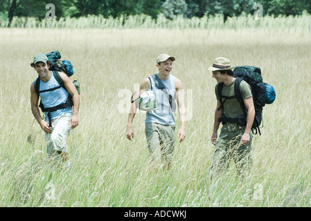 Drei Wanderer zu Fuß durch Feld, Vorderansicht - Stockfoto