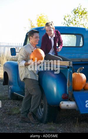 Mittleren gealterten paar entlädt Kürbisse aus alten blauen Pickup-Truck beim haben des Spaßes vertikale - Stockfoto