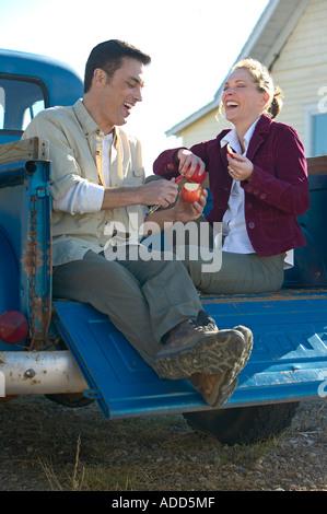 Applying paar sitzen auf der Rückseite eines alten blauen Pickup-Truck und teilen einen Apfel - Stockfoto