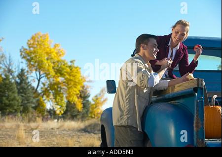 Applying paar lächelnd sitzt auf der Rückseite eines alten blauen Pickup-Truck Verzehr von Äpfeln - Stockfoto