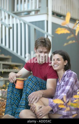 Kaukasische paar sitzt draußen mit Kaffee im Pyjama im Herbst - Stockfoto