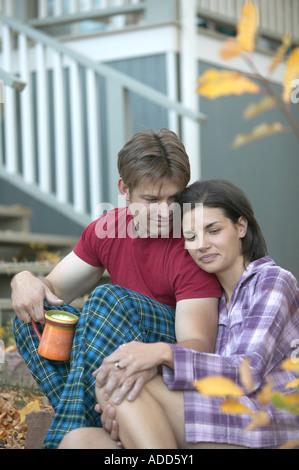 glücklich Anfang 30 kaukasische paar sitzt im Freien mit Kaffee im Pyjama im Herbst - Stockfoto