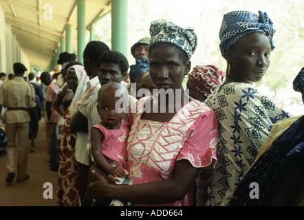 Frauen mit ihren Kindern im ländlichen Krankenhaus in Basse in Gambia Schlange - Stockfoto