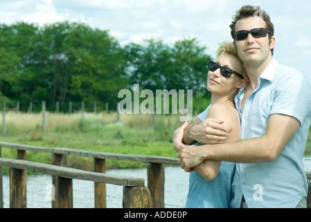 Koppeln Sie stehen durch Steg, Mann Betrieb Frau in seine Arme, beide tragen Sonnenbrillen - Stockfoto